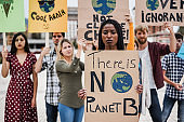 Group of demonstrators on road, young people from different cultures fight for climate change - Global warming and enviroment concept - Focus on african girl face