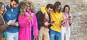 Group of friends using smart mobile phones app - Teenagers addiction to new technology trends - Concept of youth, tech, social and friendship - Focus on two right men