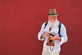 Happy hipster man using old vintage camera standing on red wall - Mature stylish photographer having fun traveling the world - Joyful elderly lifestyle concept - Focus on face