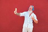 Senior hipster man using smartphone app for creating playlist - Trendy tattoo mature guy having fun with mobile phone technology - Joyful elderly lifestyle concept - Focus on left hand