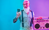 Senior hipster man using smartphone app for creating playlist - Trendy tattoo guy having fun with mobile phone technology - Tech and joyful elderly lifestyle concept - Radial purple and blue filter