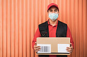 Portrait of delivery man holding a package for delivering - Focus on face
