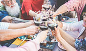Happy family and friends cheering with red wine at barbecue dinner outdoor - Different age of people having fun at sunday meal - Food, toast and summer concept - Focus on tattooed arm