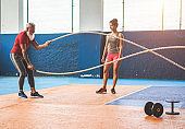 Fit man with battle rope in functional training fitness gym - Personal trainer motivating male athlete inside wellness club center - Workout and sport trends concept - Focus on man body