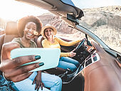 Happy girls having fun in convertible car in summer vacation - Young women friends taking selfie on cabriolet auto outdoor - Main focus on blond girl face - Travel, holidays and friendship concept