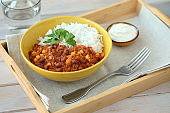 Chili con carne with rice decorated with parsley