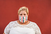 Curvy woman smiling on camera while wearing face protective mask outdoor - Coronavirus lifestyle concept
