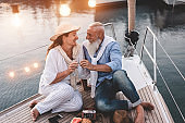 Senior couple cheering with champagne on a sailboat during summer vacation - Old people having fun together drinking and laughing - Joyful elderly lifestyle, travel and love concept