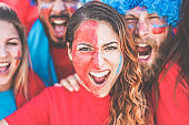 Crazy sport fans screaming while supporting their team - Football supporters with paited faces having fun inside stadium for soccer match - Event concept - Focus on right man face - Focus on girl eyes