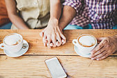 Young couple drinking cappuccino at bar coffee shop - People holding each others hands for tender love moments - Relationship concept during travel vacation - Focus on together hands