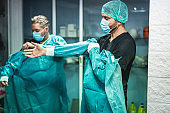 Doctors preparing to work in hospital for surgical operation during coronavirus pandemic outbreak - Medical workers getting dressed inside clinic - Focus on right man face