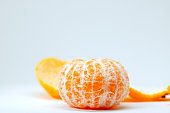 Juicy tangerine peeled off on white background. Bright orange citrus fruit. Whole tangerine without peel.