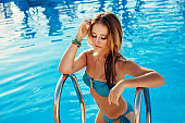 a beautiful young lady enjoys a rest in the pool, tropical holidays