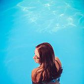fashion photo of beautiful glamour blonde in bikini with bijou posing in swimming pool