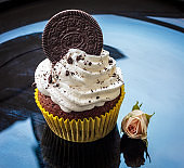 White cream cake decorated with cookies on a black plate
