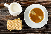 Pitcher with milk, wafers, spoon, cup with black coffee on saucer on wooden table. Top view