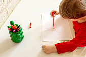 boy draws with felt pen in the album