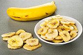 Yellow banana, banana chips on table, banana chips in white bowl