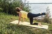Senior woman making yoga near river.