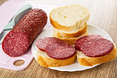 Knife, piece of sausage on cutting board, slices of bread, sandwiches with sausage in plate on wooden table
