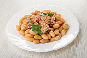 Glass plate with chicken stew, canned white beans and parsley on table