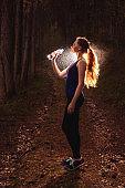 Woman drink in dark forest after run.