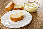 Pieces of bun, spoon in bowl with condensed milk, slice of bun in plate on wooden table