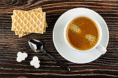 Wafers, cup with black coffee on saucer, pieces of sugar, spoon on wooden table. Top view