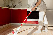 Woman cleaning house with wireless vacuum cleaner.