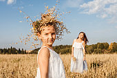 Young mother and daughter dance in field.