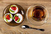 Tartlets with cream, strawberry and kiwi in brown saucer, cup with tea on saucer, spoon on wooden table. Top view
