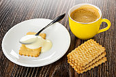 Spoon on cookie poured condensed milk in saucer, cup with coffee, cookies on wooden table
