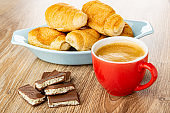 Bowl with croissants, pieces of chocolate with dairy porous filling, red cup with coffee on wooden table