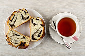 Slices of bun with poppy in plate, cup of tea, spoon on saucer on table. Top view