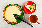 Pie in plate, knife, section of sour cream pie with spearmint in saucer, cup with tea on wooden table. Top view