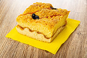 Cake with apricot jam and prune on paper napkin on table