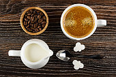 Bowl with coffee beans, cup with coffee, pitcher with milk, spoon, pieces of sugar on wooden table. Top view