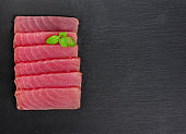 Fresh raw tuna steak with basil. On black rustic background