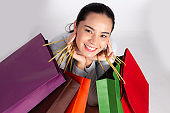 Cheerful beautiful Asian woman holding multi coloured shopping bags and shows ok sign on light White background.