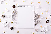 Top view of blank notebook on white wooden background with xmas decorations, copy space. Christmas background with notebook for wish list or to do list, red gift boxes, fir tree branches. Flat lay