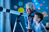 Grandson with grandfather stargazing at night with a telescope