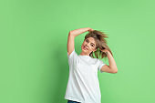 Caucasian young woman's portrait on green studio background