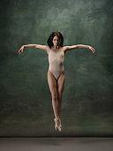 Young graceful tender ballerina on dark green studio background