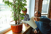 Grandfather and his grandson spending time insulated at home, having fun, caring for plants, watering