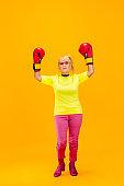 Senior woman in ultra trendy attire isolated on bright orange background