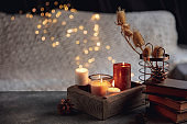 Burning candles in the wooden box isolated on grey and white background with garland lights. Greeting card design.
