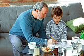 Grandfather and his grandson spending time insulated at home, stadying, writing, drawing or playing together