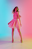 Beautiful seductive girl in fashionable, romantic outfit on bright gradient pink-blue background in neon light