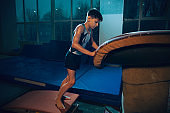 Little male gymnast training in gym, flexible and active