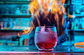 Close up of alcoholic cocktail, beverage, drink in multicolored neon light with fire flames on the background